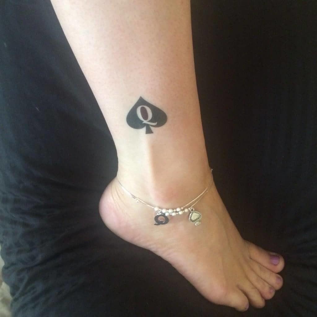 Imagen de tatuaje y pulsera tobillera con el símbolo de cuckold como avalorio